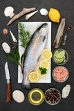 Rainbow Trout Healthy Heart Food. On crushed ice with rustic knife, herbs, peppercorns, olive oil, himalayan salt, lemon and lime on slate background. High in Stock Photos