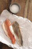 Rainbow Trout Meat on a Table with Salt. Top View of Fresh Rainbow Trout Meat on a Paper Placed on Wooden Table with Rock Salt on a Saucer Royalty Free Stock Photos