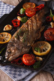Rainbow trout with vegetables on a grill pan close-up. Vertical Royalty Free Stock Photo