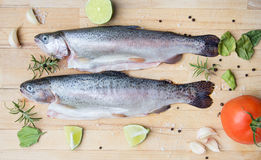 Rainbow trouts on wooden cutting board. Rainbow trouts with lemon on wooden cutting board royalty free stock photo