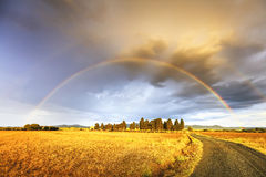 Rainbow in Tuscany, cypress trees and rural road. Maremma, Italy Stock Photos