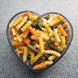 Rainbow Twirls. Colored and regular rotini twirls / twists in a heart shaped dish Royalty Free Stock Photos