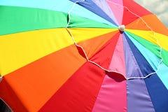 Rainbow Umbrella. Large multi-colored rainbow beach umbrella and sky stock photos