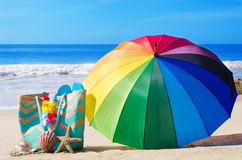Rainbow umbrella and beach bag. Summer background with rainbow umbrella, white hat and bag on the sandy beach Stock Image