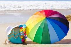 Rainbow umbrella and beach bag Stock Images