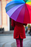 Rainbow Umbrella. Beautiful and stunning french girl taking a walk through town with her amazing colorful rainbow umbrella, wearing a long warm red coat a winter Royalty Free Stock Images