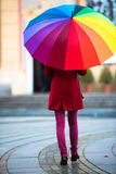 Rainbow Umbrella. Beautiful and stunning french girl taking a walk through town with her amazing colorful rainbow umbrella, wearing a long warm red coat a winter Royalty Free Stock Image
