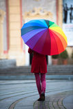 Rainbow Umbrella. Beautiful and stunning french girl taking a walk through town with her amazing colorful rainbow umbrella, wearing a long warm red coat a winter Stock Photos