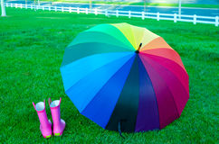 Rainbow umbrella with boots on the grass Stock Photos