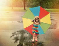 Rainbow Umbrella Child Walking in Park. A little girl is walking with a rainbow umbrella in her hand and rubber boots outside at a park for a weather or season stock photography
