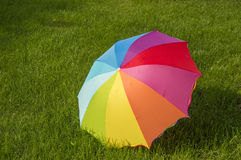 Rainbow umbrella on the grass Stock Images