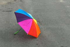 Rainbow umbrella lying on the pavement after the summer rain, forgotten by a child. Sadness and loneliness. Stock Photos