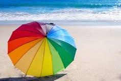 Rainbow umbrella by the ocean Royalty Free Stock Image