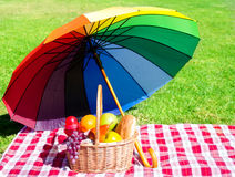 Rainbow umbrella and Picnic basket Stock Image