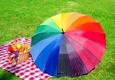 Rainbow umbrella and Picnic basket Royalty Free Stock Photo