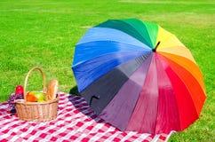 Rainbow umbrella and Picnic basket Royalty Free Stock Photos