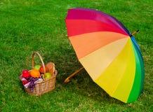 Rainbow umbrella and Picnic basket Royalty Free Stock Photography