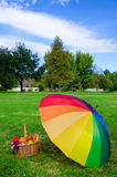 Rainbow umbrella and Picnic basket Stock Photography