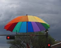 Rainbow Umbrella In Pride Parade Edmonton 2018. Rainbow umbrella against a dark and cloudy sky in Edmonton, Alberta`s pride parade June 9, 2018 stock photos