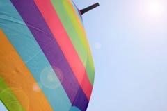 Rainbow umbrella sun protector on sky Stock Photo