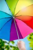 Rainbow umbrella in woman hands on nature background. Focus on the latch closing umbrella stock photos