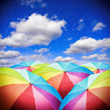 Rainbow umbrellas against the sky with rain. Background. focus on the foreground umbrellas Stock Images