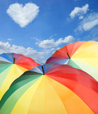 Rainbow umbrellas on blue sky background Stock Image