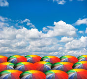 Rainbow umbrellas on cloudy sky Royalty Free Stock Images
