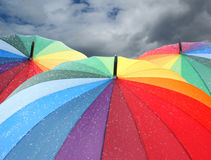 Rainbow umbrellas with snowflakes Stock Image