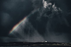 Rainbow Under Dark Clouds City at Distance Royalty Free Stock Photography