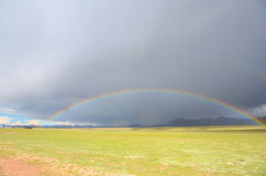 The rainbow under the dark clouds in Tibet Stock Images
