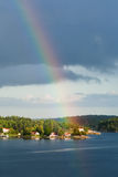 Rainbow under small village on seashore Stock Photography