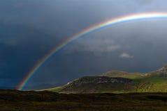 Rainbow V2. Rainbow with dark sky over a meadow Royalty Free Stock Image