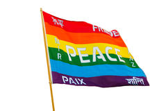 Rainbow varicolored pacifist flag with multilingual peace text i Stock Image