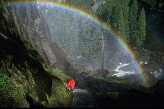 Rainbow at Vernal Falls, Yosemite. Hiker under rainbow (created by mist from Vernal Fall) wearing red poncho on Mist Trail, Yosemite National Park, California Stock Image