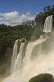Rainbow visible in the drops of water thrown out by the thundering waterfalls of Iguazú. Stock Photos