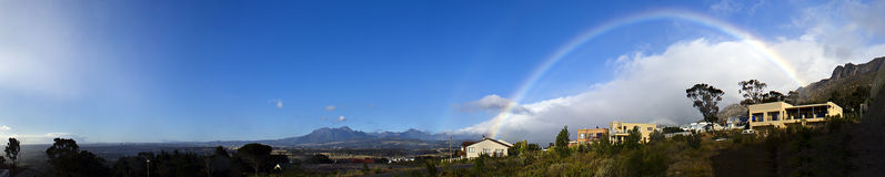 Rainbow Vista. A well placed rainbow — the pot of gold being a beautiful guest house, I've stayed in. Gordons Bay, South Africa Royalty Free Stock Image