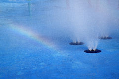 Rainbow and water fountain background Stock Photos