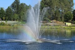 Rainbow from a water fountain in a small lake Royalty Free Stock Photo
