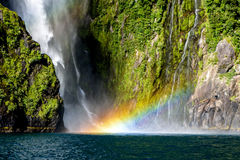 Rainbow on waterfall Milford Sound in New Zealand stock photos