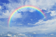Rainbow with white clouds over sky Stock Photo