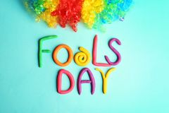 Rainbow wig and phrase. `Fools day` made from plasticine on color background. 1st April celebration Royalty Free Stock Image