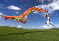 Rainbow woman. Young beautiful woman jumping with a scarf Stock Photography