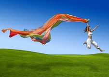 Rainbow woman. Athletic woman jumping on a green meadow Royalty Free Stock Photography