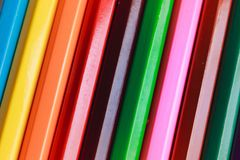 Rainbow wooden wallpaper from pencils. Colored pattern Stock Photos