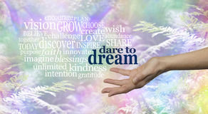 Rainbow Woodland Dare to Dream word cloud. Female hand outstretched palm up on a rainbow woodland background and the words DARE TO DREAM floating above stock photo