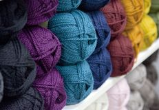 Rainbow of yarn or wool on a shelf. Blue, green, yellow, purple, red yarn bundled and sitting on a shelf at home, in a craft room or store Stock Image