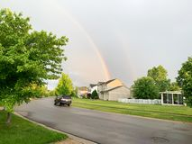 Rainbowl over city  Michigan. Rainbow over the city of  Ann Arbor, Michigan USA. Rainbow over the blue sky in spring, residential area. Closeup. Background stock photo