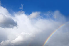 Rainbows. Two rainbows in the sky filled with white clouds stock photo