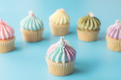Rainbows cupcake muffin on blue background. Rainbows cupcake muffin on blue pastel background Royalty Free Stock Photo